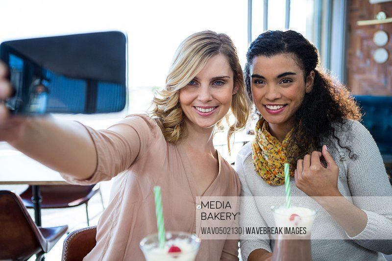 Smiling female friends taking a selfie on mobile phone in cafeteria
