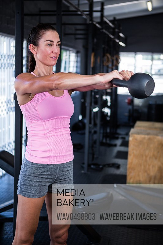 Young woman holding kettlebell while standing in gym