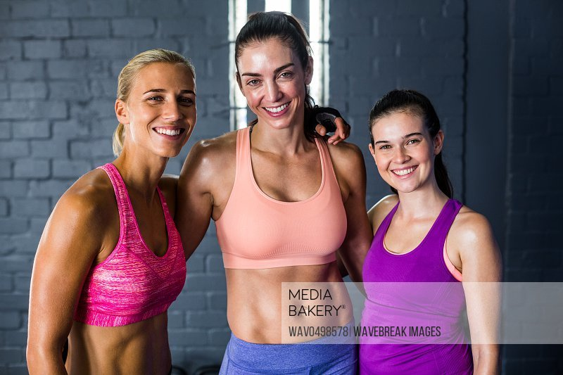 Portrait of smiling female athletes standing against wall in gym