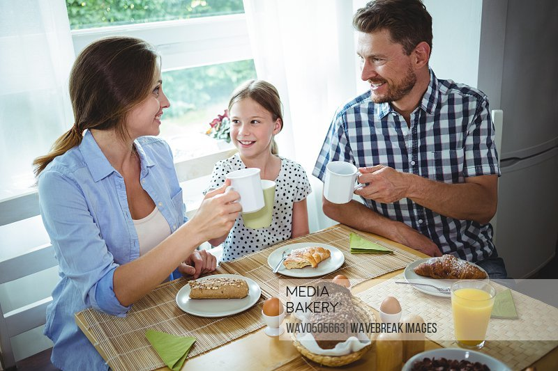Family toasting a cup of coffee while having breakfast at home