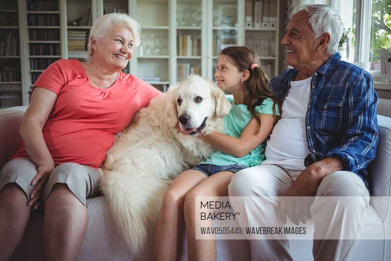 Happy grandparents and granddaughter sitting with pet dog at home