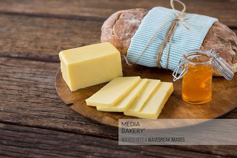 Slices of cheese bread and fruit jam on wooden board