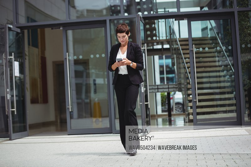 Businesswoman using mobile phone in office premises