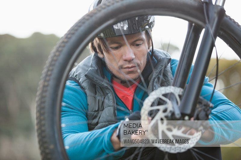Male mountain biker examining front wheel of his bicycle in the forest