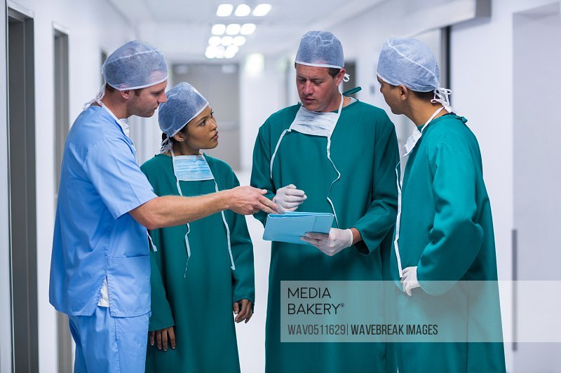 Surgeons and nurse having discussion on file in corridor of hospital