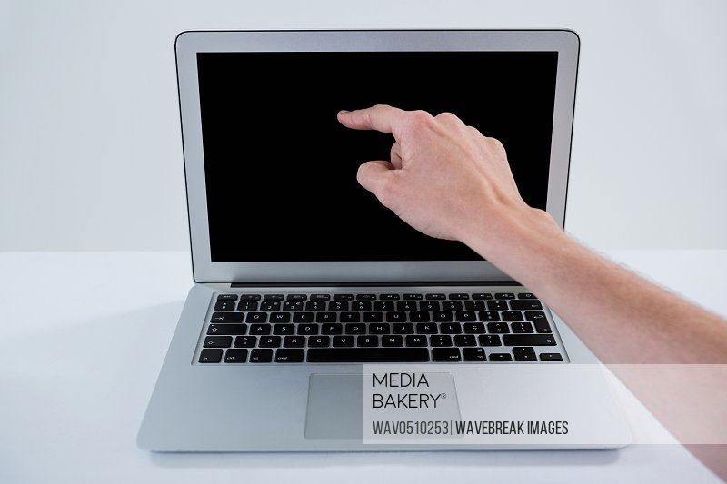 Hand of man pointing at laptop