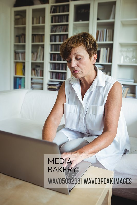 Senior woman sitting on sofa and using laptop in living room