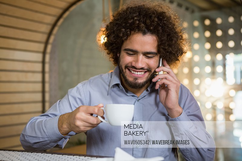 Man talking on mobile phone while having cup of tea in bar