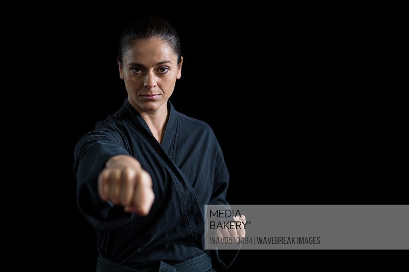Portrait of female karate player performing karate stance against black background