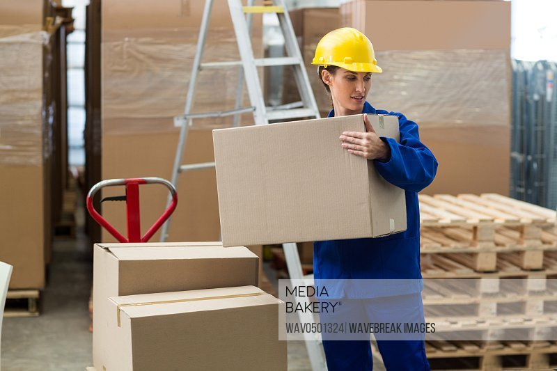 Delivery worker unloading cardboard boxes from pallet jack in warehouse
