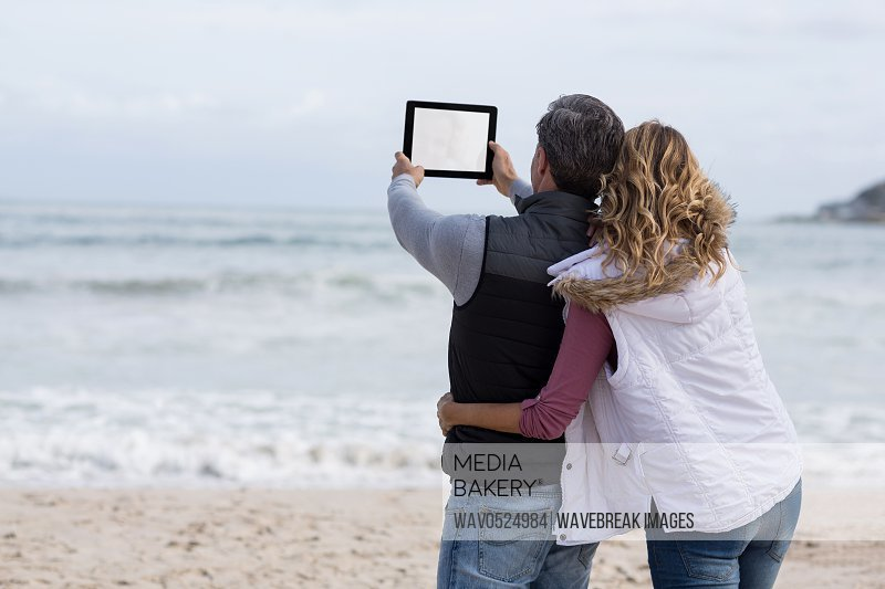 Mature couple taking selfie with digital tablet