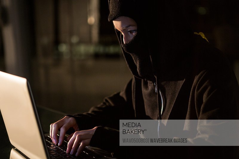 Woman in balaclava using laptop in the office