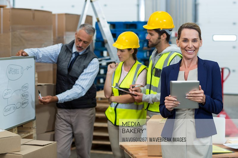 Portrait of warehouse manager holding digital tablet in warehouse and colleagues discussing in background