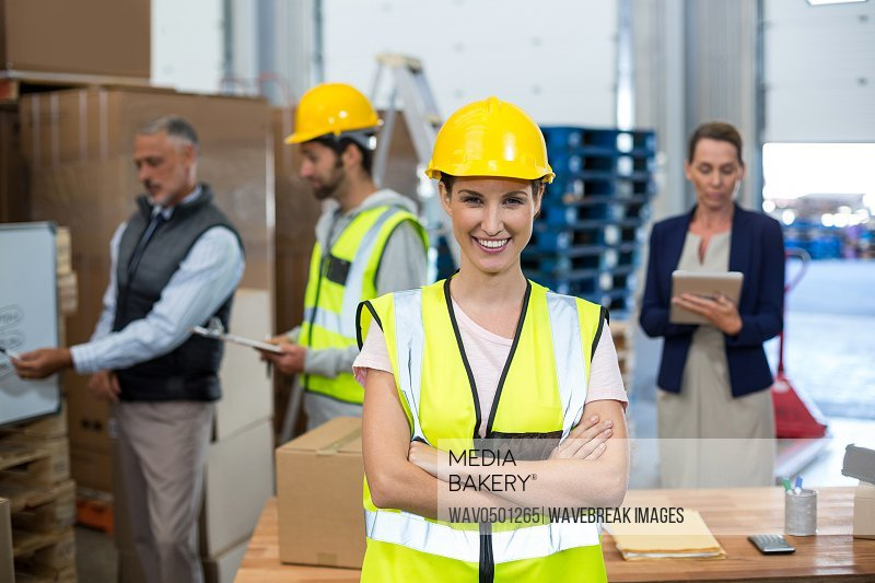Portrait of female warehouse worker standing with arms crossed in a warehouse