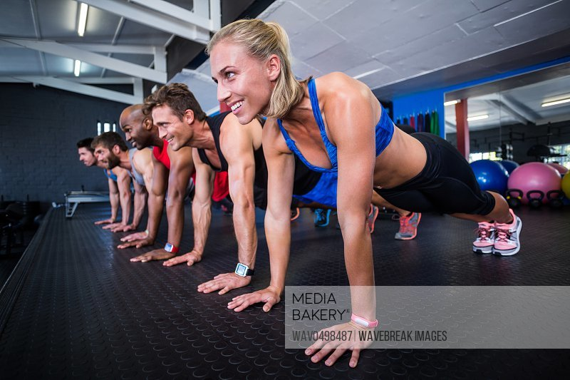 Smiling friends doing push-ups while exercising in gym