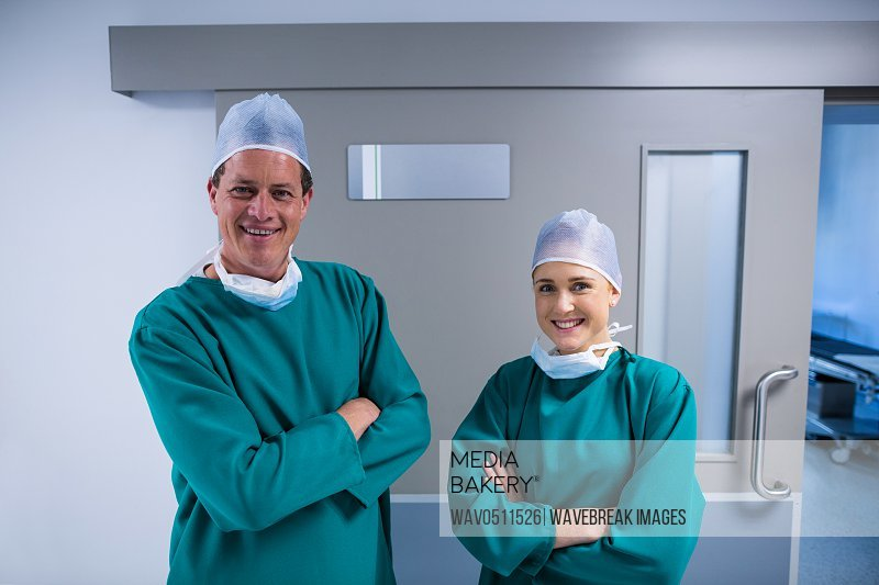 Portrait of happy surgeons standing with arms crossed in corridor of hospital