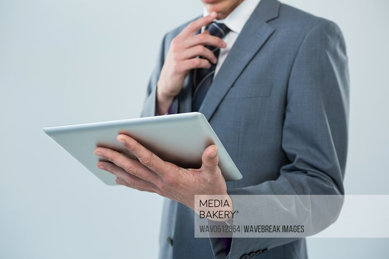 Mid section of businessman looking at digital tablet against white background