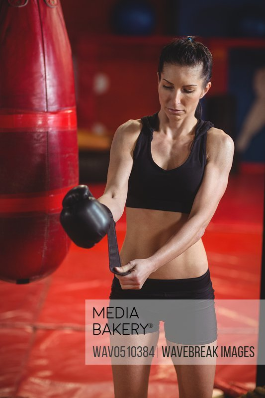 Female boxer wearing boxing gloves in fitness studio