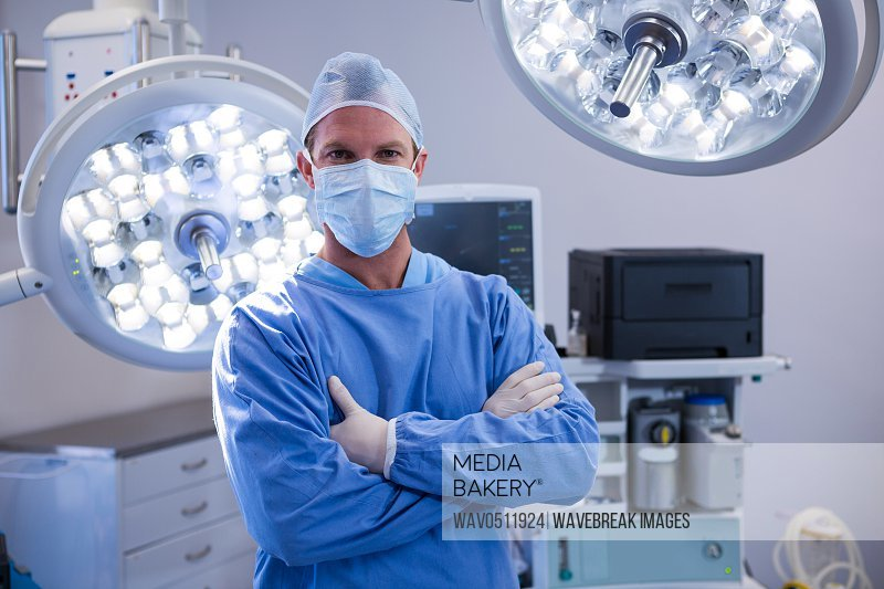 Portrait of male surgeon standing with arms crossed in operation theater