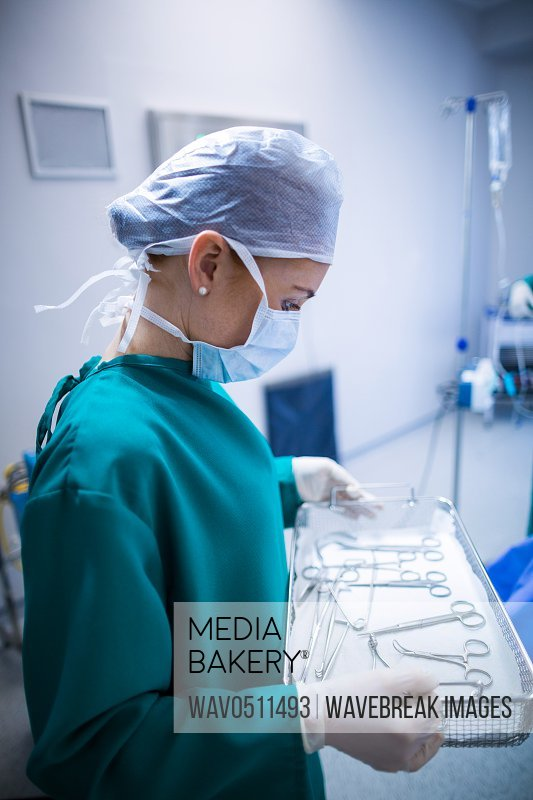 Female surgeon holding surgical tray in operation theater of hospital