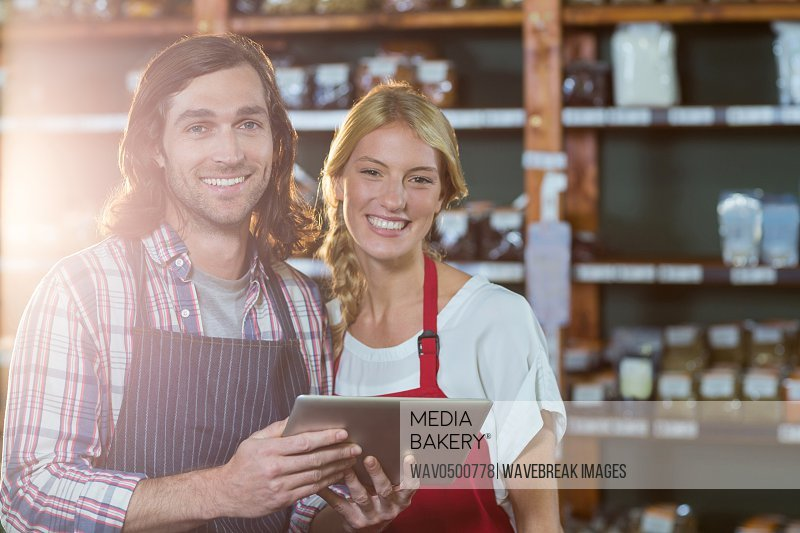 Portrait of smiling staffs using digital tablet in organic section of supermarket