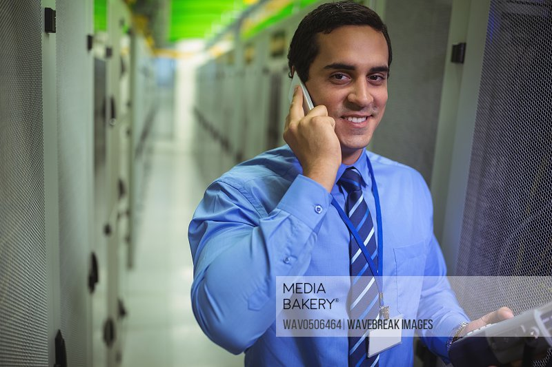 Portrait of technicians talking on mobile phone while analyzing server in server room