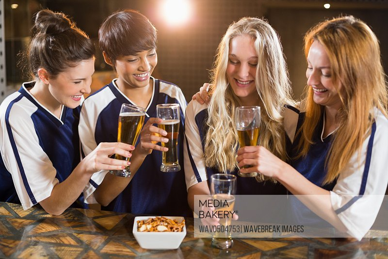 Portrait of smiling friends toasting glass of beer in party at bar