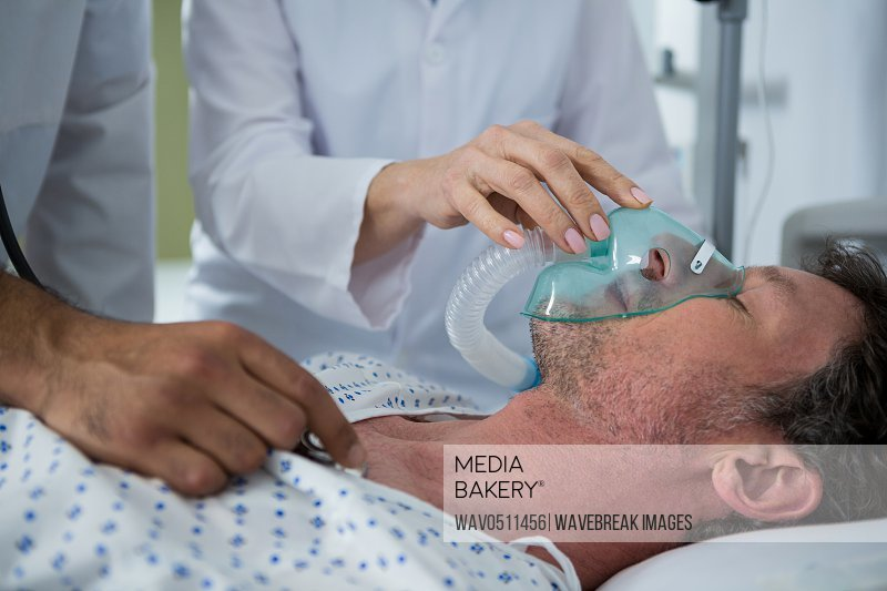 Doctor placing an oxygen mask on the face of a patient in hospital