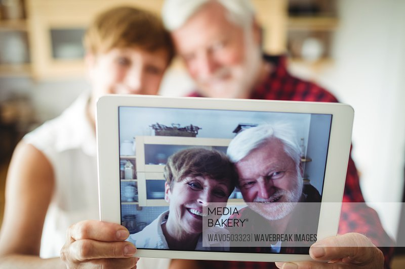 Senior couple clicking a picture on digital tablet in kitchen