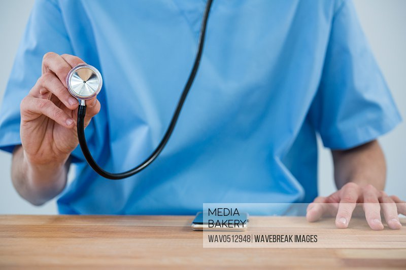 Mid section of Male nurse holding stethoscope against white background