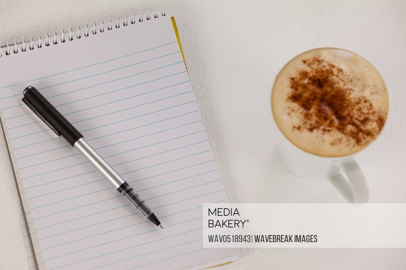 Cup of coffee with spiral notepad and pen