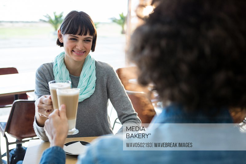 Smiling couple toasting glass of cold coffee in cafeteria