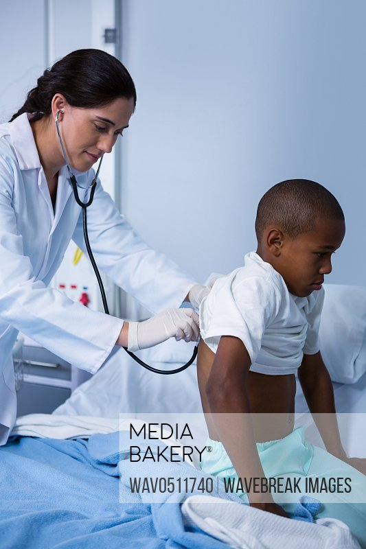 Doctor examining patient with stethoscope in ward at hospital