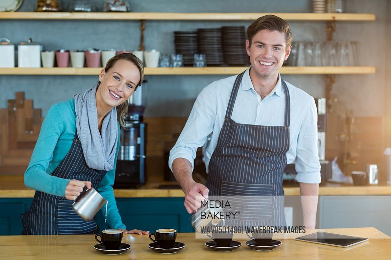 Portrait of smiling waiter and waitress making cup of coffee at counter in cafe