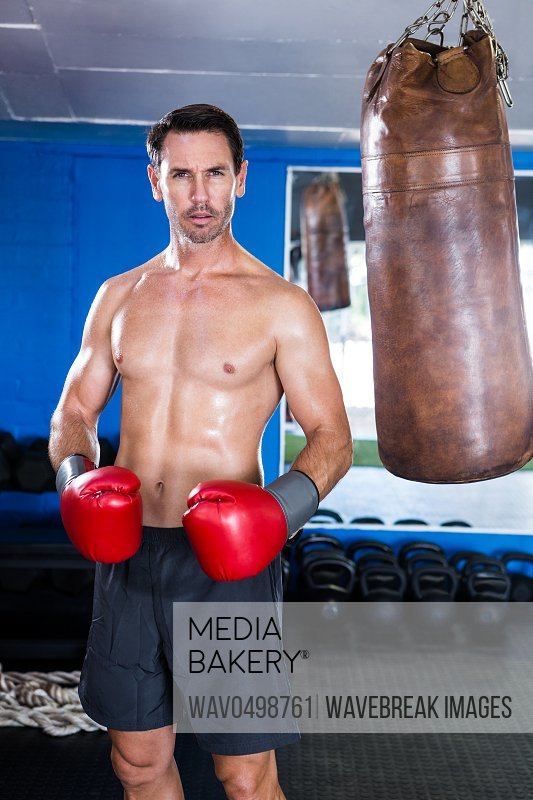 Portrait of serious shirtless boxer standing in gym