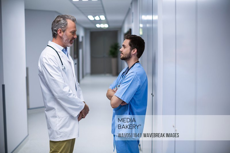 Doctor and male nurse interacting with each other in corridor of hospital