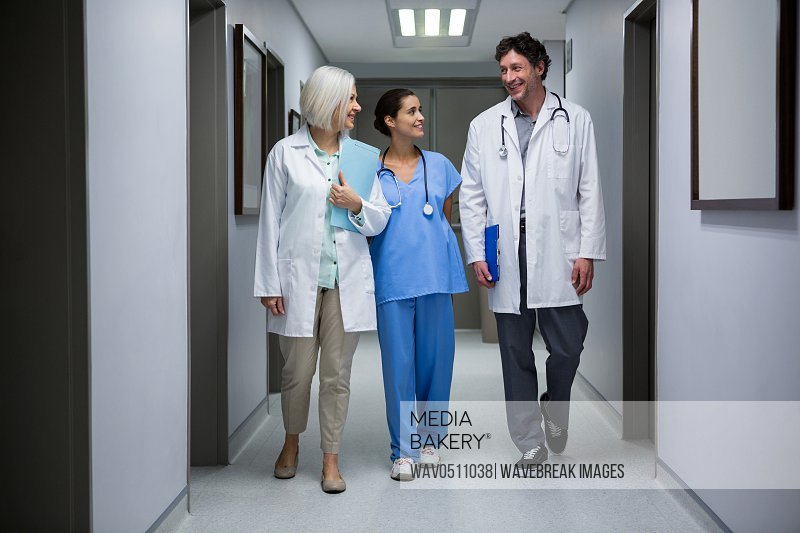 Doctors and surgeon interacting while walking in corridor at hospital