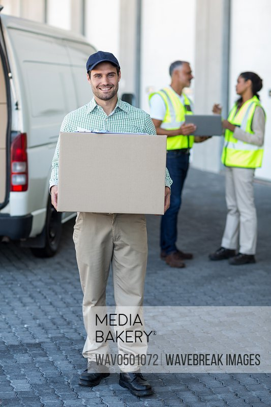Portrait of delivery man carrying cardboard box outside the warehouse