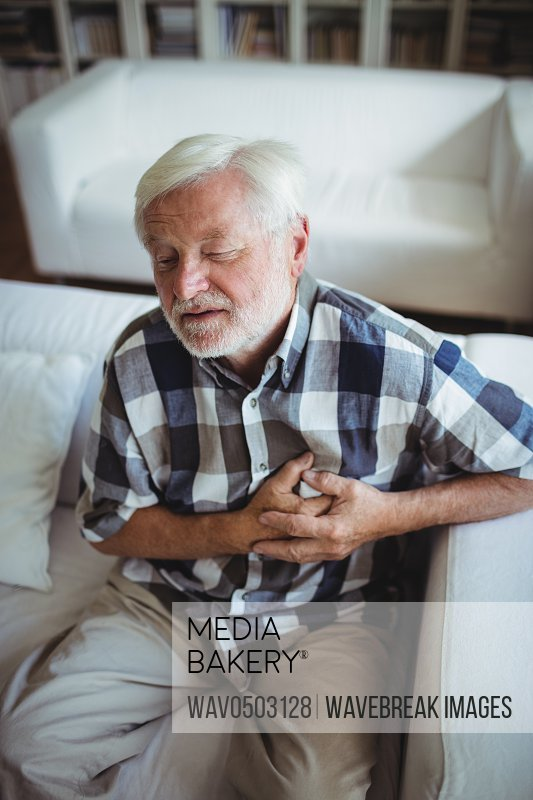 Senior man suffering from chest pain at home