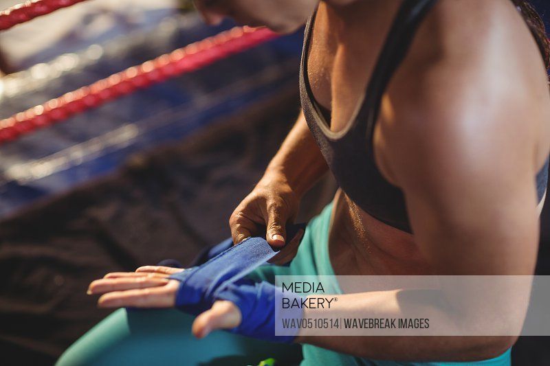 Female boxer wearing blue strap on wrist in boxing ring