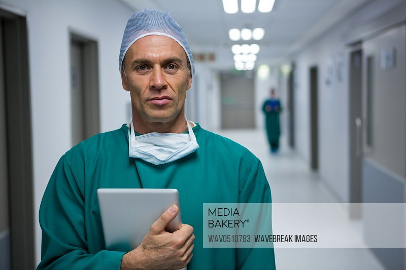 Portrait of male surgeon standing with digital tablet in corridor of hospital