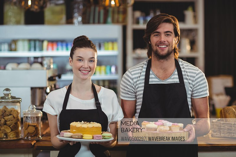 Portrait of waiter and waitress holding a tray of cupcakes in cafe