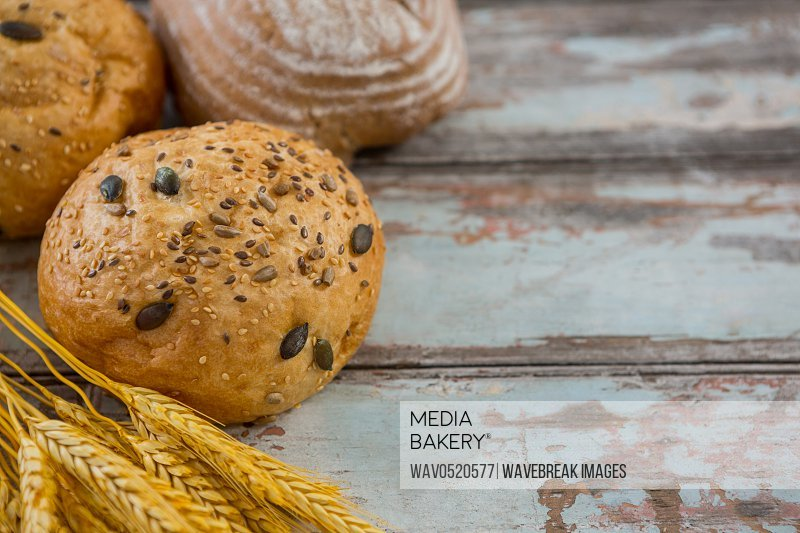 Bread loaf with wheat on wooden table