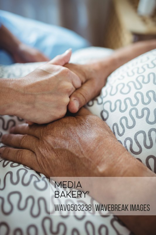 Close-up of nurse holding hands of senior woman in bedroom