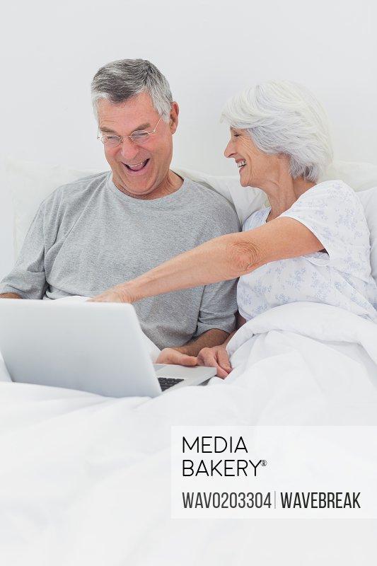 Mature woman pointing at husbands laptop