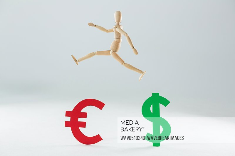 Wooden figurine jumping over dollar and euro symbol against white background