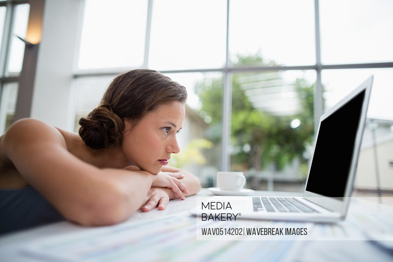 Businesswoman leaning on desk and looking at laptop