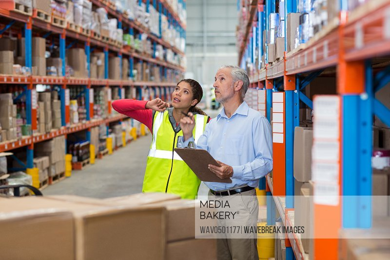 Warehouse manager and female worker interacting while checking inventory in warehouse