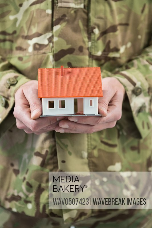 Mid section of soldier holding a model home against white background