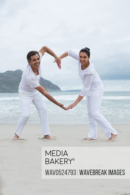 Romantic couple making heart by hands on beach